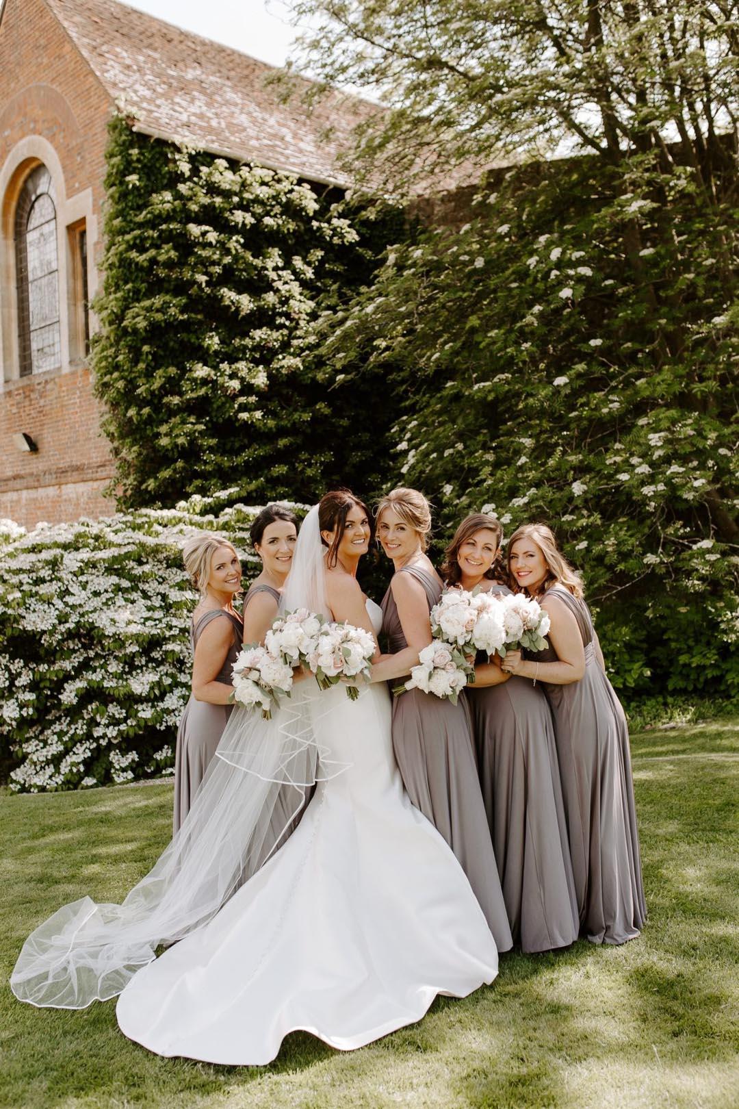 Bridesmaids wearing long grey dresses at Farnham Castle