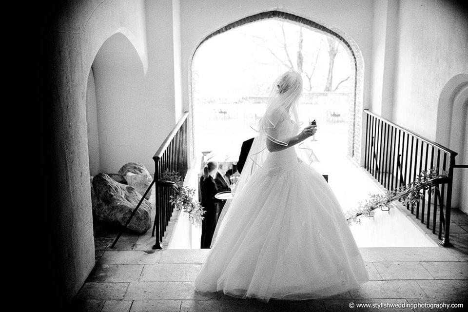 Bride looking down the steps of Farnham Castle