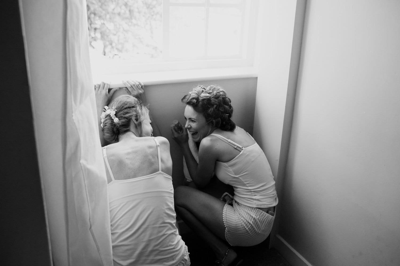 Bride and bridesmaid hiding below the window