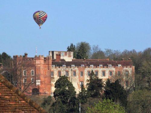 Hot air balloon rising above Farnham Castle